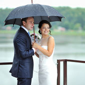 Bride and groom portrait on their wedding day by the rain — Stock Photo