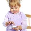 Adorable little girl using mobile phone on white background — Foto Stock