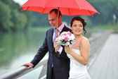 Bride and groom in the rainy day — Stock Photo