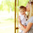 Beautiful mother kissing her adorable little son outdoors  — Stock Photo