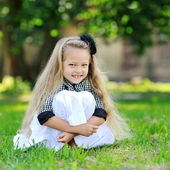 Sweet little girl sitting in a grass and smiling — Stock Photo