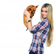 Beautiful woman holding her little puppy near a copyspace and lo — Stock Photo