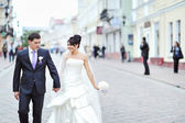 Bride and groom walking together in an old town — Stock Photo
