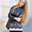 Fashion model wearing sunglasses with bag smiling outdoors — Stock Photo