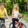 Attractive happy couple on a bicycles in a countryside — Stock Photo