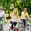 portrait of attractive young woman on bicycle and two men in blu — Stock Photo