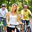 Portrait of attractive young woman on bicycle and two men behind — Stock Photo