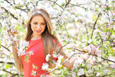 Portrait of a beautiful woman in blooming spring tree — Stock Photo