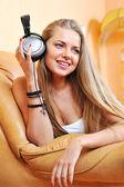 美丽的女孩拿着耳机听音乐 — 图库照片