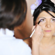 Stock Photo: Young beautiful bride applying wedding make-up by make-up artist