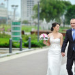 Stock Photo: Bride and groom walking together in old town