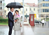 Bride and groom hiding from rain in an old town — Stock Photo