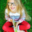 Adorable little girl in glasses holding book and laughing - outd — Stock Photo