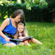 Mother and daughter reading book in a park — Stock Photo