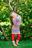 Adorable little girl posing in a park and folding her arms near — Stock Photo
