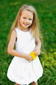 Sweet little girl with flower in a park - outdoor portrait — Stock Photo