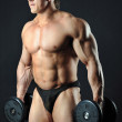 Bodybuilder holding dumbbells - studio portrait — Stock Photo