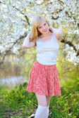 Beautiful girl posing in blooming tree on nature — Stock Photo