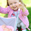 Cute little girl with her toy carriage - closeup portrait — Stock Photo