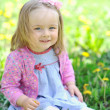 Cute little girl sit on the meadow in summer day — Stock Photo