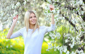 Portrait of beautiful woman in blooming spring tree — Stock Photo