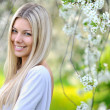 Portrait of attractive beautiful blonde woman in green blooming — Stock Photo #25372197