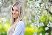 Portrait of attractive beautiful blonde woman in green blooming — Stock Photo