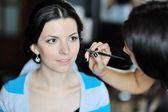 年轻漂亮的新娘应用婚礼化妆的化妆师 — 图库照片