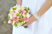 Bride holding wedding bouquet in hands — Stock Photo