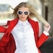Young lady in red dress posing outdoors wearing sunglasses — ストック写真