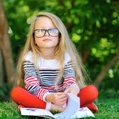 Portrait of sweet little girl wearing glasses, reading book, sit — Stock Photo
