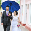 Young happy wedding couple walking by the rain in an old town — Stock Photo