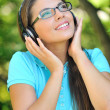 Beautiful young woman with headphones outdoors. Enjoying music — Stock Photo #27589335