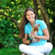 Beautiful smiling young woman with small dog, against green of s — Stock Photo