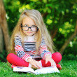 Sweet little girl wearing glasses and reading book in a park — Stock Photo