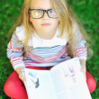 Adorable little girl with a book wearing glasses - outdoors — Stock Photo