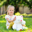 Sweet little girl outdoors with a toy bear — Stock Photo #28650037