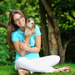 Young beautiful girl hugging her little dog near a copyspace  — Stock Photo