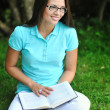 Young teenage girl wearing glasses with book in a park — Stock Photo