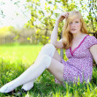 Beautiful girl sitting on a meadow — Stock Photo
