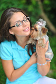 Attractive young girl playing with her yorkshire terrier puppy o — 图库照片