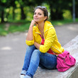 Beautiful girl sit in a park with hand on chin — Stock Photo