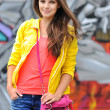 Young woman in bright clothes posing outdoors — Stock Photo