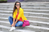 Beautiful girl in colorful clothes wearing sunglasses — Stock Photo