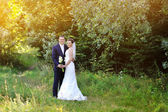 Young happy bride and groom in a park. Wedding couple — Stockfoto