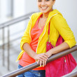 Beautiful young girl in colorful clothes with bag — Stock Photo