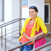 Beautiful smiling woman in colorful clothes with bag — Stock Photo