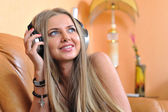 Attractive young girll listening music through headphones — Stock Photo