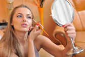 Young beautiful woman applying make-up - portrait — Stock Photo
