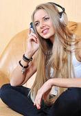 Aantrekkelijke jonge vrouw luisteren muziek via de koptelefoon — Stockfoto